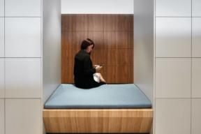 Female employee sitting on locker bank bench. Configurable Workplace Lockers - Personal Storage Lockers